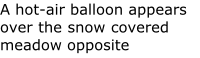 A hot-air balloon appears over the snow covered meadow opposite